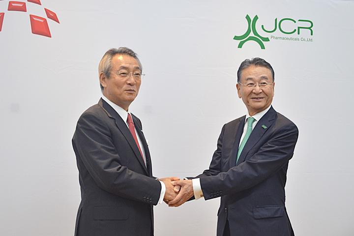 握手を交わすメディパルHDの渡辺社長(左)とJCRの芦田会長兼社長=22日、東京都内